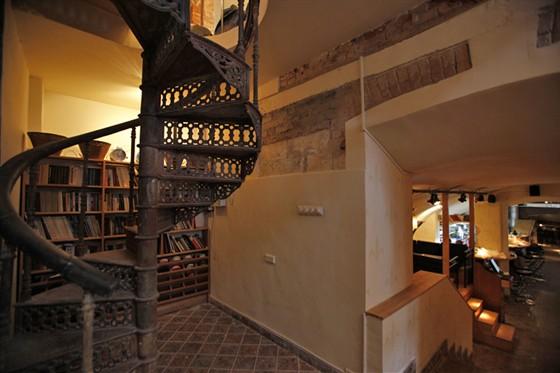 Ресторан FAQ-Café - фотография 11 - Винтовая лестница (ведет на VIP-балкон) и книжный шкаф с прибитыми внизу ячейками для тапочек друзей клуба.